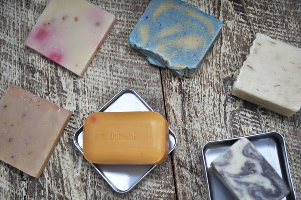 Image of several different types of shampoo bars on a wooden surface